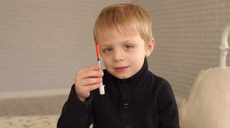 cukorbaj : A little boy sitting on the bed at home and holding an insulin syringe. Slow motion.