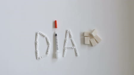 薬と健康管理 : Composition with the word DIA from insulin syringes, lancets and sugar cubes on a white background. The view from the top. 動画素材