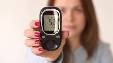 glicose : A woman is sick with type 1 diabetes, she holds a glucometer with a good level of glucose in the blood. Slow motion. The good compensation sugar diabetes. The concept of type 1 and type 2 diabetes. 4K Stock Footage