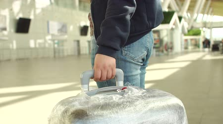 queue : Female hands hold the suitcase handle while standing in line at the airport. Concept of tourism and travel. Close-up. Close-up of a woman holding a suitcase which is packed in protective film. Stock Footage