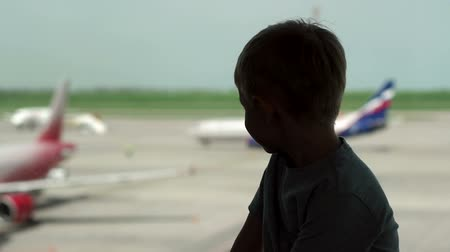 chegar : The silhouette of a little boy near a large window at the airport, he looks at the planes. Slow motion.