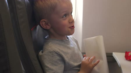 respiração : Close-up portrait of a little boy on a plane, he is vomits and he is holding a special package for vomiting. The kids vomits on the plane, hes vomiting. Slow motion.