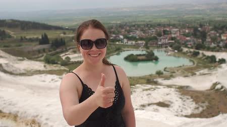 travertine : Young girl looking on travertine pools and terraces in Pamukkale. Cotton castle in southwestern Turkey. Young woman enjoying the views on travertine pools and gives a thumbs up in Pamukkale. Slow mo.