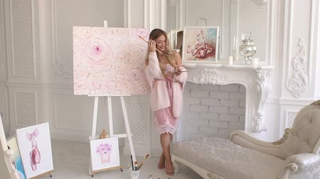 Portrait of a cute young girl in a pink knitted sweater with a palette of colors in her hands in an art studio. Slow motion. Young tender girl paints on canvas at home in bedroom. Stock Footage