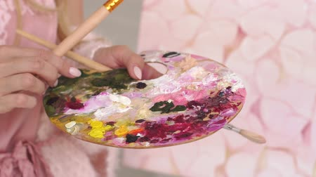 Close-up of the girl holding a large palette of paints and brushes for drawing. Art, hobby, teaching drawing.