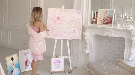 A talented girl artist with long hair in a delicate pink long sweater is admiring her painting in the drawing studio. Portrait of an artist girl near a picture with flowers. Stock Footage