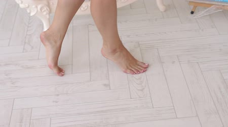 haunches : Close-up of the girls legs of the artist with bare feet, she walks along a light laminate with easels and paintings on it. Slow motion. Stock Footage