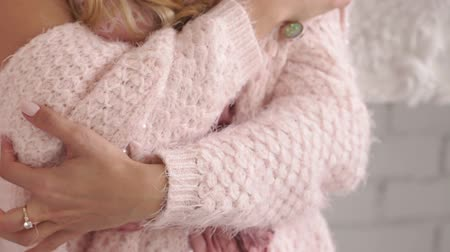 Close-up of a young girl wrapped in a warm pink knitted sweater at home. The gentle girl is dressed in a pink negligee and a knitted sweater.Close-up of hands. Slow motion.