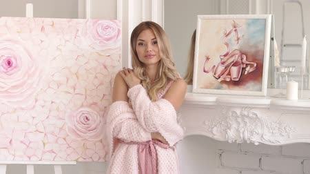 A young gentle artist girl in a pink negligee and a delicate knitted sweater stands near a painted picture with pink flowers at home in the bedroom.Portrait of a young artist near the painted pictures