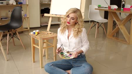 A luxurious blonde with red lips poses in the drawing Studio, she is dressed in jeans and a white shirt. A young girl with a palette and brushes sitting on the floor in an art Studio. Stock Footage