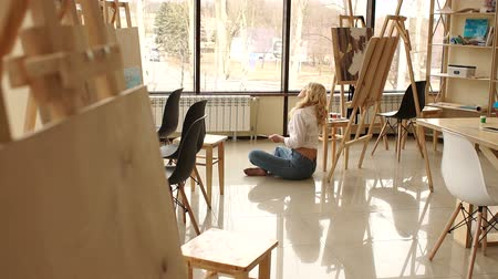 A young sexy girl in jeans and a white shirt sits on the floor leaning against a wooden easel, she holds a palette with tassels and looks out the big window. 무비클립