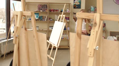 Portrait of a dreamy young girl artist in the Studio for drawing. Girl artist in a white shirt with bright makeup and red lipstick, she walks around the drawing Studio among easels and paintings. 무비클립