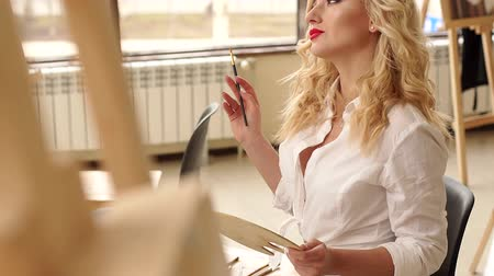 A beautiful girl in a white shirt with brushes for drawing in her hand sits in the Studio among easels and paintings. Portrait. Slow motion. Stock Footage