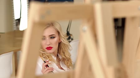 A sweet thoughtful girl with blond curly hair and red lips draws a picture in the studio. Portrait of a delicate artist girl with a tassel in her hands. Slow motion.