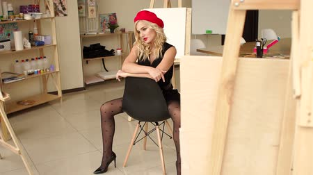 мольберт : Portrait of a talented sexy girl in an art Studio among easels, paintings and various art equipment, she sits on a chair in a black dress with a red hat. Slow motion.