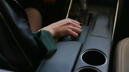 Close-up of a girl sitting in her new car at a car dealership and moving her hand through the control panel, steering wheel and the interior of the car. Happy girl sitting in her new car.