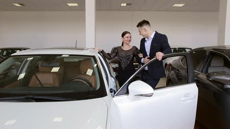 A young couple in love buys a car in the showroom. Buying or renting a car. Sale or rent a car.