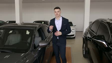Portrait of a successful happy young man in a suit in the showroom with the keys to a new car in his hands, he bought a new Executive car.