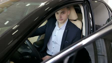 sala de exposição : A successful self-confident man chooses a new car in the showroom, he sits behind the wheel and carefully examines everything.
