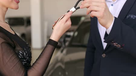 A man car salesman gives a luxurious girl in a black dress the keys to a new car. Close-up.