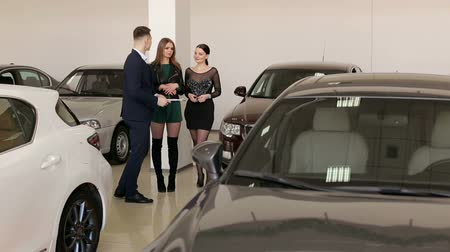 A handsome man car salesman is talking to two charming girls in a car dealership among many different cars. Two girls came to the showroom to choose a new car. Stock Footage