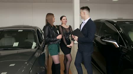 A handsome man car salesman is talking to two charming girls in a car dealership among many different cars. Two girls came to the showroom to choose a new car. Vídeos