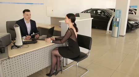 An elegant girl in a black dress talking to a car salesman sitting at a table in the showroom, they sign documents and make a deal. Stock Footage