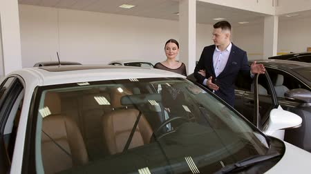 Young couple watching a new white car in the showroom of the dealership. Happy young couple choose a new modern car in the showroom. Vídeos