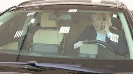 A successful young businessman in a suit talking on the phone while sitting behind the wheel in his new car in the showroom. Portrait of a businessman in a car with a phone. Vídeos