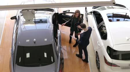 Car salesman talking to customers in the showroom, he talks about the characteristics of the machine and shows the documents. The process of selling cars in the showroom. Stock Footage