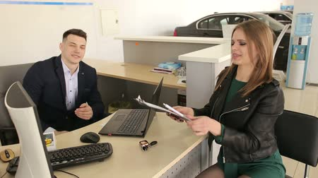 Young businesswoman signing some documents at the table with salesperson or manager buying or renting car in the showroom. Young woman and salesman sitting at table in car salon. Buying auto