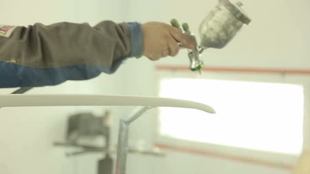 compressor : Worker painting a car parts in a paint booth. Spray gun with paint for painting a car. Automobile repairman in protective workwear painting car body bumper. Stock Footage