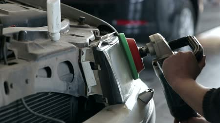 A professional mechanic grinds the car body before painting. The mechanic works at the service station with a grinding machine. Grinding the car body close-up. Stock Footage