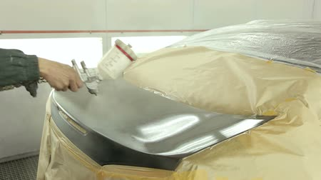 repaint : Mechanic paints black paint the rear hood of the car at the service station in a specialized painting room. Painting the car by a professional painter at the service station. Stock Footage