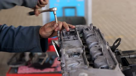 Close-up hands of unrecognizable mechanic doing car service and maintenance. The process of working at the service station, close-up. Stock Footage