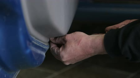 Close-up of a mechanic with dirty hands repairing the engine from the car at the service station. Close-up hands of unrecognizable mechanic doing car service and maintenance.