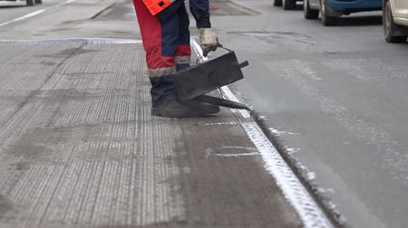 yama işi : Road repair. Work details, workers pour resin road surface to cover the asphalt. Men in specialized clothing repair asphalt in the city. Preparation of asphalt pavement for laying new asphalt.