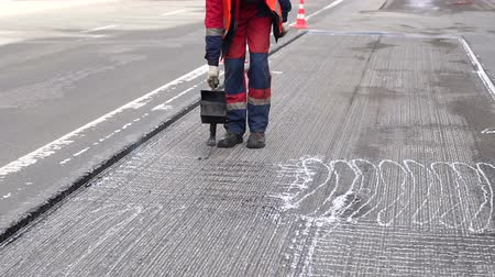 Road repair. Work details, workers pour resin road surface to cover the asphalt. Men in specialized clothing repair asphalt in the city. Preparation of asphalt pavement for laying new asphalt.