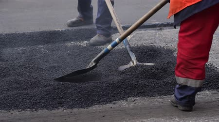 yama işi : Workers on a road construction, industry and teamwork. Fresh asphalt construction. Bad road. Roller and workers on asphalting and repair of city streets. Close-up.