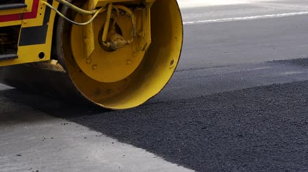 Close-up of an asphalt rink lays new asphalt on the road. Repair of roads. The repair work of industrial machines in the city.