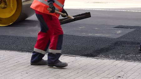 Łopata : Worker leveling fresh asphalt on a road construction site, industrial buildings and teamwork. Road works.