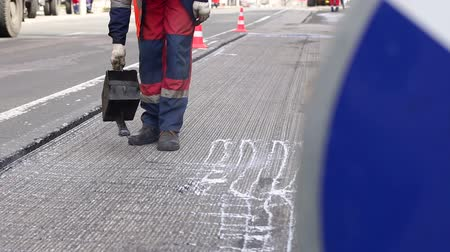 paving : Road repair. Work details, workers pour resin road surface to cover the asphalt. Men in specialized clothing repair asphalt in the city. Preparation of asphalt pavement for laying new asphalt.