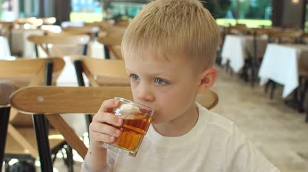sede : Close-up of a small happy emotional boy having Breakfast in a restaurant, he drinks juice. Slow motion. In the background, a blurred image of a crowded restaurant.