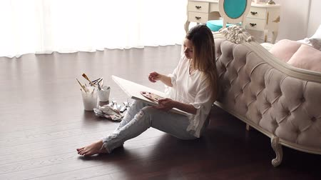 peonias : Sexy girl in ripped jeans and white blouse draws at home sitting on the floor near the bed. Slow motion. Archivo de Video