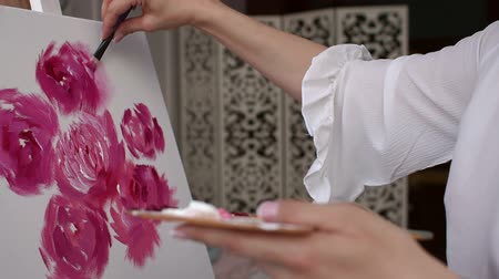 мольберт : Close-up girl paints peonies with brush on the canvas. The artist paints pink flowers on canvas with brush, close-up. Стоковые видеозаписи
