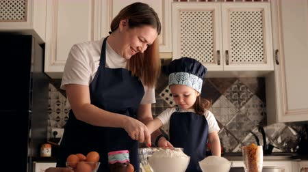 mladé ženy : Happy laughing mother with a little cute daughter prepare dessert together in the kitchen. Portrait of happy smiling mother and daughter making pies together at the kitchen.