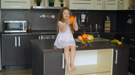 muz : Little girl sitting on the kitchen table Stok Video