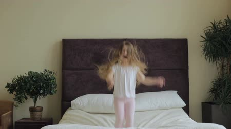 salto : Little girl jumping on the bed at home