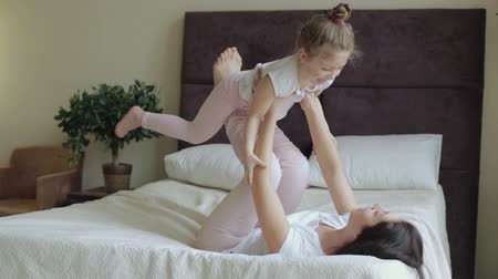 вниз : Mother and daughter lying and playing on the bed at home