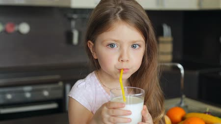 delicioso : Little girl drinking milk through a straw from a glass